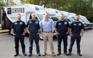 The team at TE Electric standing in front of trucks