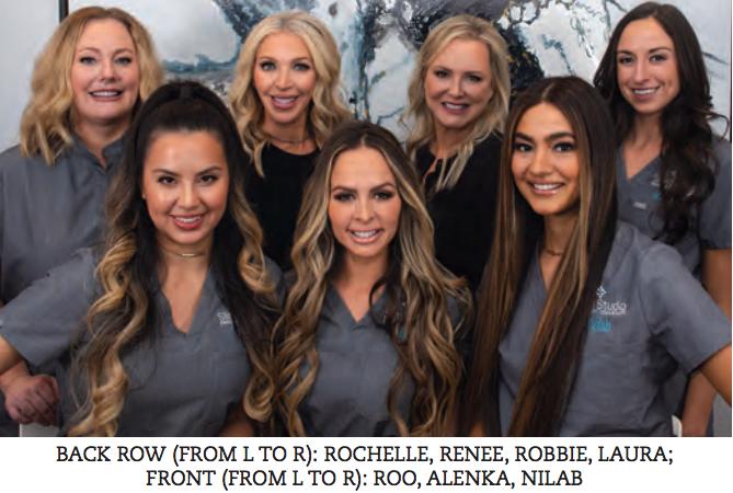 A group of women wearing gray scrub smiling at camera