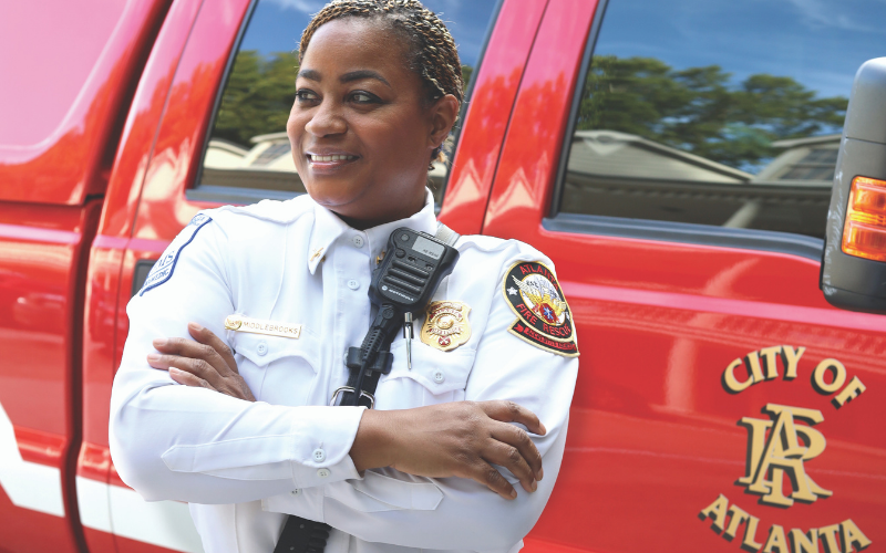 Michelle Middlebrooks standing in her fire uniform in front of a red Atlanta fire truck