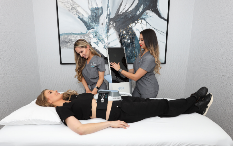 Two women in gray scrubs helping apply emsculpt machine to stomach