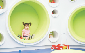 Little girl sitting in a play area
