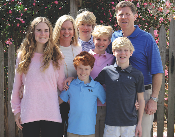 The Neumann Family dressed in pink in front of flowers