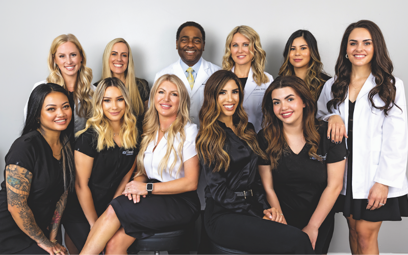 The Timeless Aesthetics team in front of a white wall wearing black scrubs