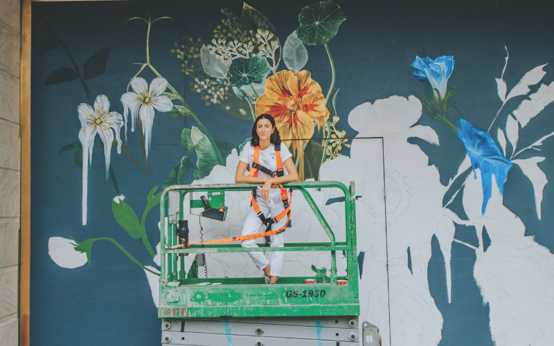 A girl in front of a mural