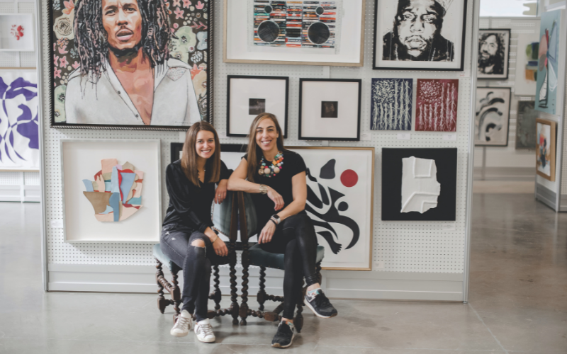 two girls sitting in front of art work